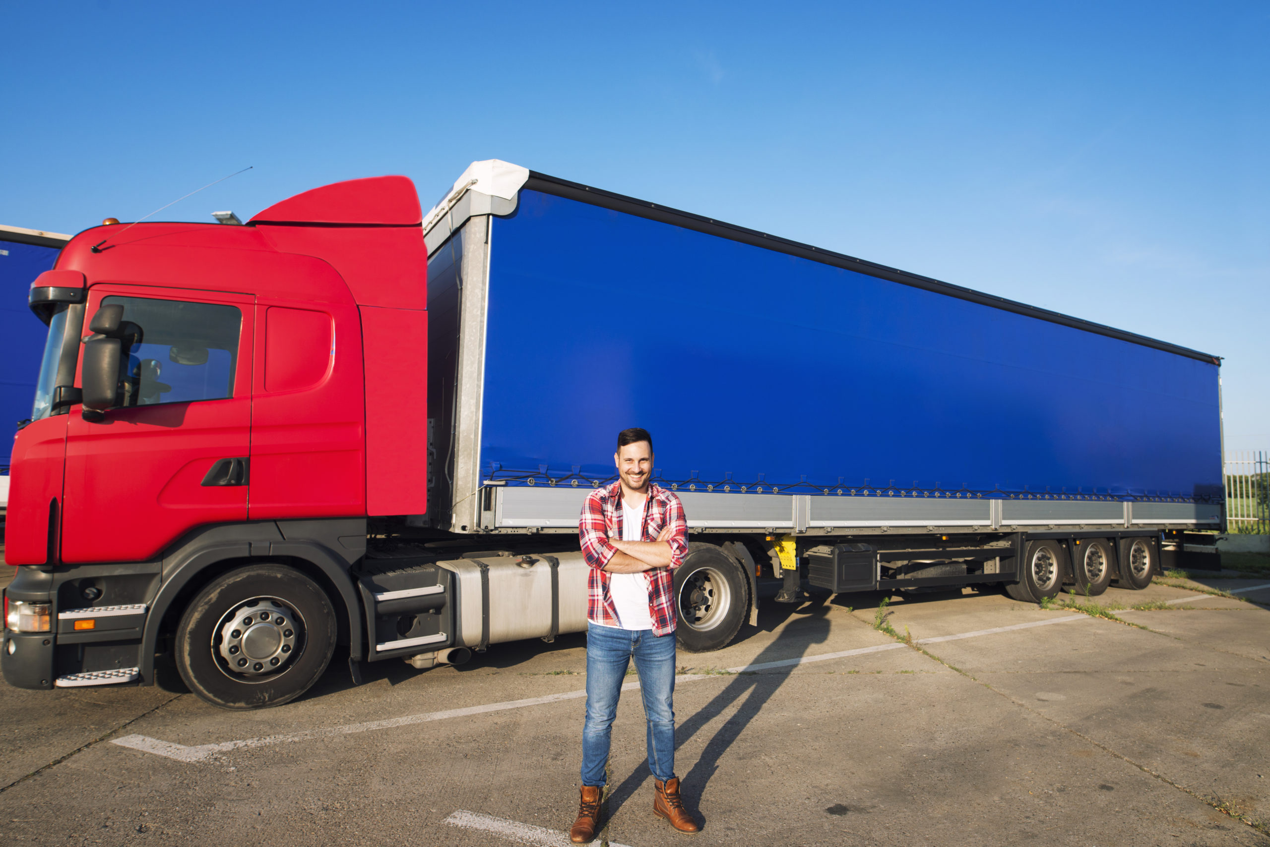 Portrait of professional American truck driver in casual clothing and boots standing in front of truck vehicle with long trailer.